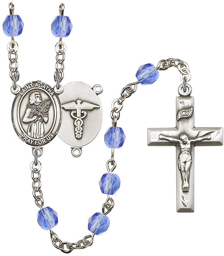 Silver Plate Rosary features 6mm Sapphire Fire Polished beads. The Crucifix measures 1 3/8 x 3/4. The centerpiece features a St. Agatha/Nurse medal. Patron Saint Nurses/Breast Cancer